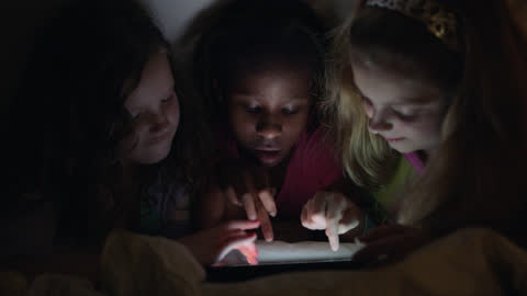 three girls playing games on digital tablet tap on touchscreen repeatedly under a cozy bedsheet fort at a fun sleepover party. - interactivity stock videos & royalty-free footage