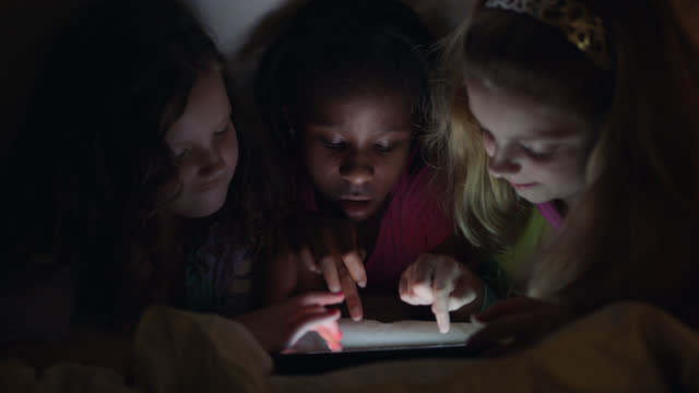 three girls playing games on digital tablet tap on touchscreen repeatedly under a cozy bedsheet fort at a fun sleepover party. - 手提 個影片檔及 b 捲影像