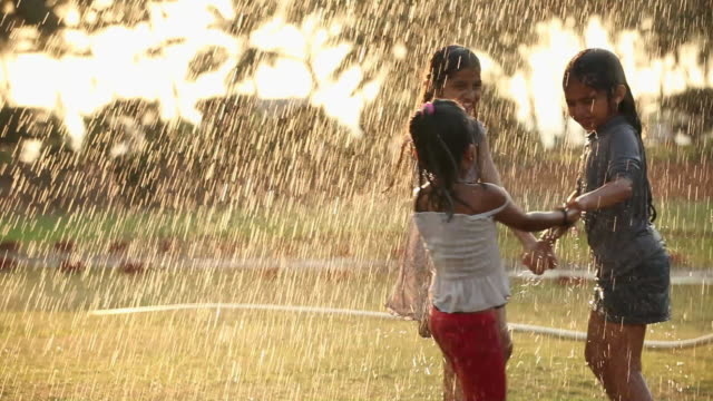 vídeos de stock, filmes e b-roll de three girls playing in front of a lawn sprinkler in a park - aspersor