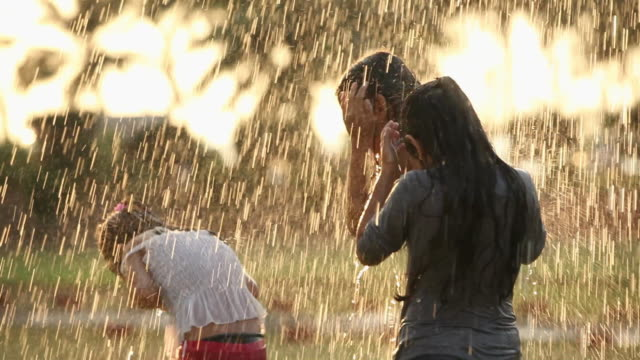 Three girls playing in front of a lawn sprinkler in a park