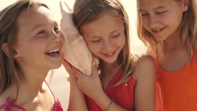 three girls playing on beach listening to conch shell. - seashell stock videos and b-roll footage