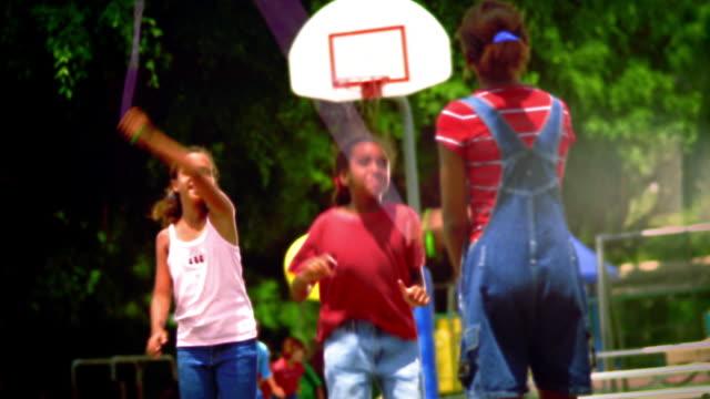 canted ms three girls playing with jump rope on playground / florida - hopprep rep bildbanksvideor och videomaterial från bakom kulisserna