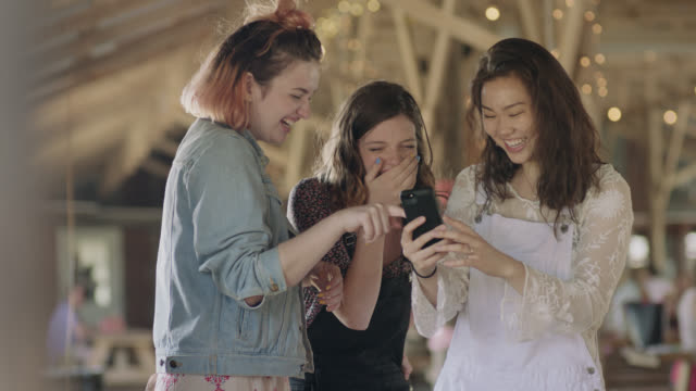 ws slo mo. three girls point at smartphone and laugh in outdoor picnic shelter. - ridere video stock e b–roll
