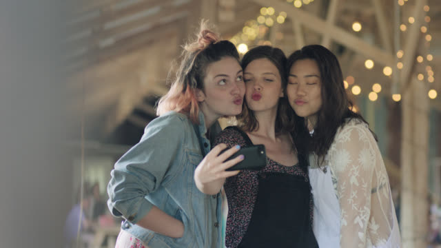ws slo mo. three girls pose for selfie with kiss faces, look at smartphone, and laugh. - drei personen stock-videos und b-roll-filmmaterial