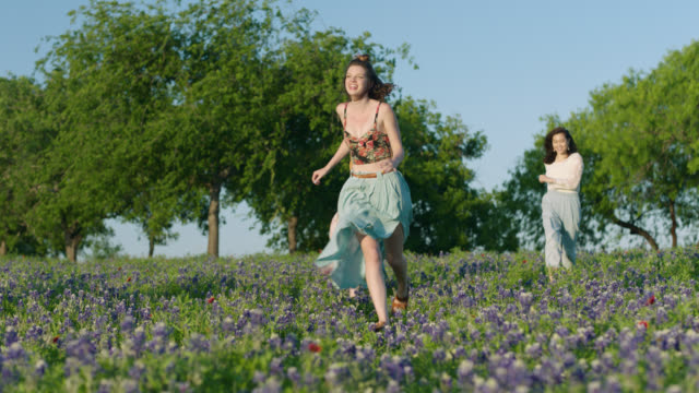 WS SLO MO. Three girls run through field of flowers on beautiful sunny day.
