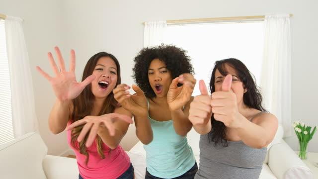 Three girls singing and waving hands