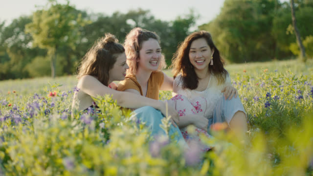 ws slo mo. three girls sit and laugh in field of flowers. - 20 24 år bildbanksvideor och videomaterial från bakom kulisserna