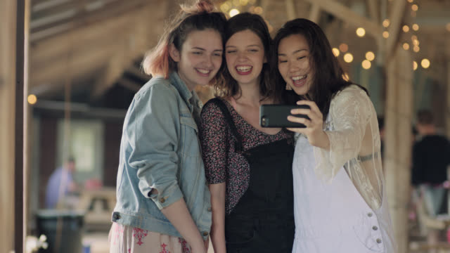 WS SLO MO. Three girls take selfies with smartphone in rustic Austin restaurant.