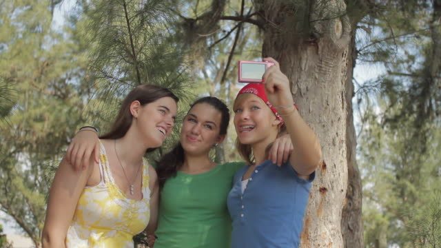 ms three girls (14-15) taking self portrait photo in forest / cape coral, florida, usa - cape coral stock videos & royalty-free footage