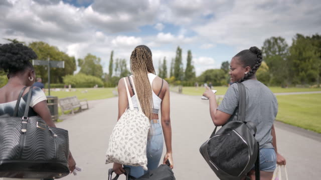 three girls together walking away from the camera in the park - three people stock videos & royalty-free footage