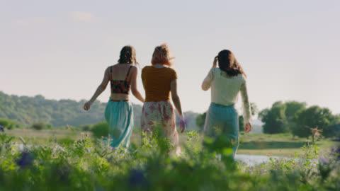 ws slo mo. three girls walk through green field toward pond on sunny day. - erwachsene person stock-videos und b-roll-filmmaterial