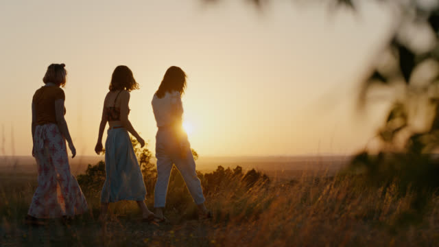WS SLO MO. Three girls walk through mountain field at sunset and look out over valley.