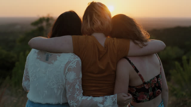 MS SLO MO. Three girls watch sunset from scenic mountain overlook.
