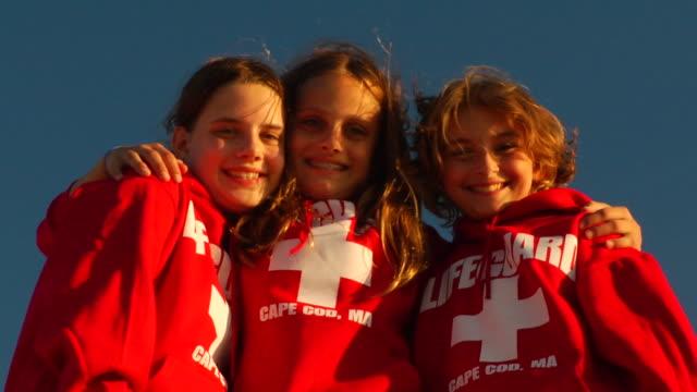 cu, la, three girls (10-11, 12-13) wearing beach lifeguard blouses, portrait, provincetown, massachusetts, usa - 12 13 år bildbanksvideor och videomaterial från bakom kulisserna