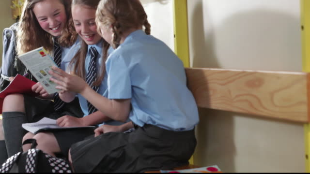 ms three girls wearing school uniforms, sitting on bench, talking, laughing  and looking through books / great yarmouth, england, united kingdom - school uniform stock videos & royalty-free footage