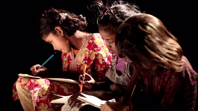 three girls writing on a book - developing countries stock videos & royalty-free footage