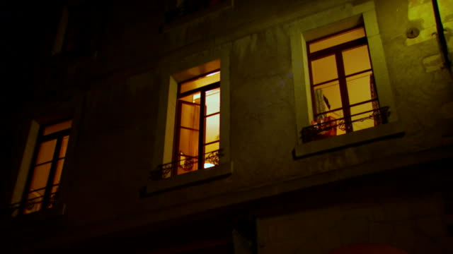 vídeos de stock, filmes e b-roll de three glowing window at night, zoom in, pan, slow motion - apartamento
