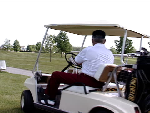 three golf carts w/ senior male golfers driving, leaving area next to tee box, driving onto paved cart, tracking one car onto fairway. - golf cart stock videos & royalty-free footage