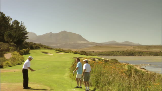 Three golfers prepare for a game on a golf course on the coast of Cape Town.