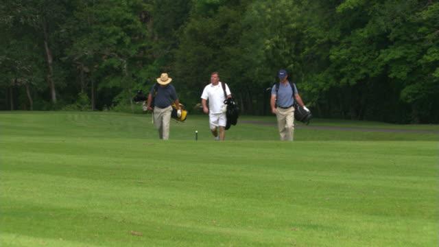 vídeos y material grabado en eventos de stock de three golfers - campo de golf links