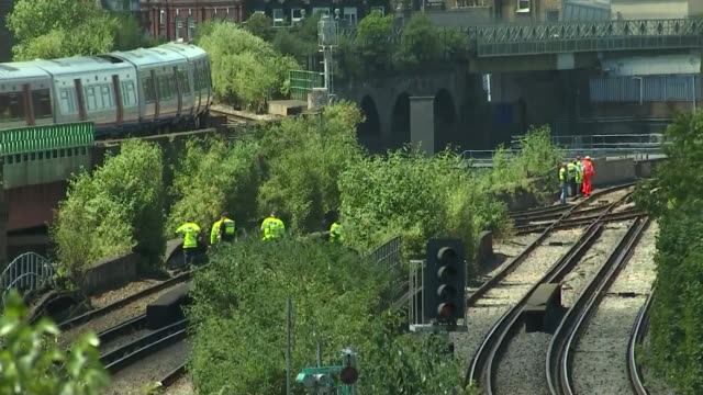 three graffiti artists killed by passing train; england: london: loughborough junction: ext members of the emergency services on railway line sat... - railway junction stock videos & royalty-free footage