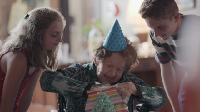 three great-grandchildren watch their great-grandmother open a birthday present inside a gift bag during her 100th birthday party - birthday gift stock videos & royalty-free footage