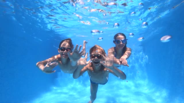 vídeos de stock e filmes b-roll de three happy kids swimming underwater in pool - três pessoas
