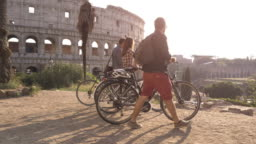 Three happy young friends tourists with bikes and backpacks at Colosseum in Rome arriving on hill at sunset with trees slow motion steadycam