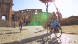 Three happy young women friends tourists riding bikes at Colosseum in Rome, Italy at sunrise.