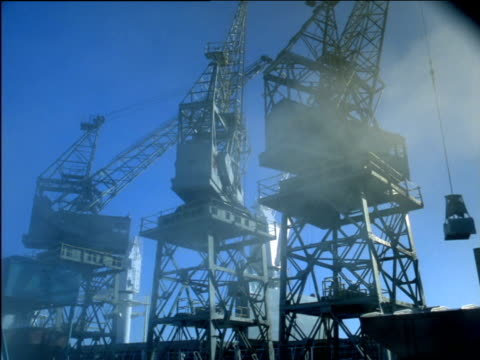 vídeos de stock e filmes b-roll de three harbour cranes pivot lowering cradles as smoke drifts past, south africa - baixar