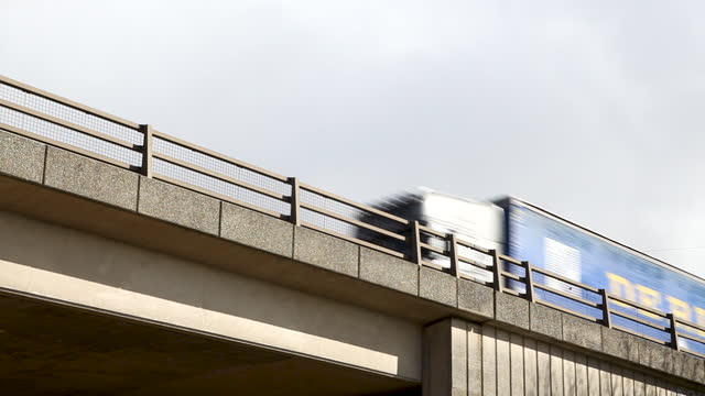 three heavy goods vehicles travelling over a concrete bridge, viewed from a low angle with copy space - low angle view stock videos & royalty-free footage