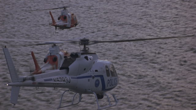 vidéos et rushes de three helicopters fly over the water to shore. - hélicoptère