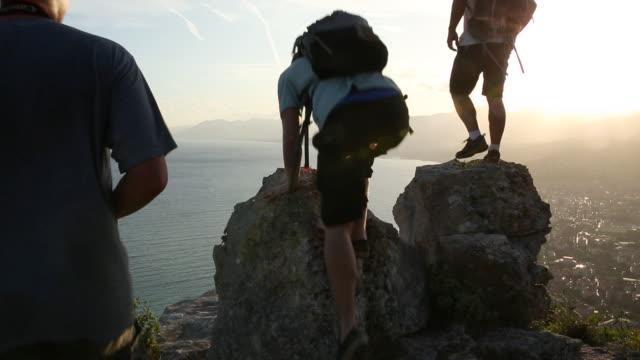 vidéos et rushes de trois randonneurs montent le bluff de roche, regardent à travers la mer - trois personnes