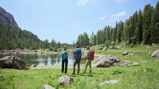 Three hikers enjoying the mountain lake view in sunshine