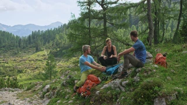 vídeos de stock, filmes e b-roll de três caminhantes a descansar pelo caminho de montanha - mãos juntas