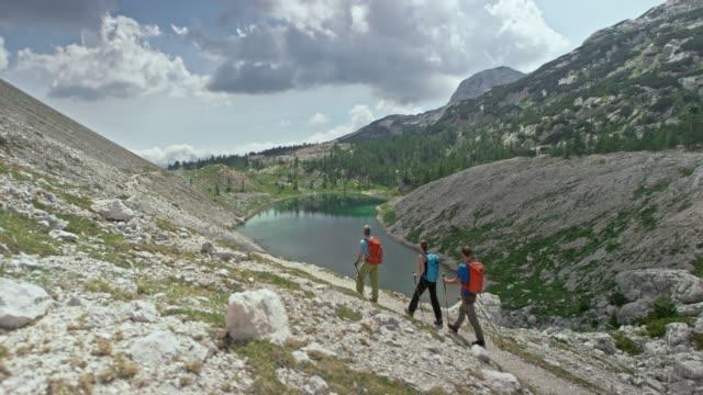 Three hikers walking on a narrow mountain path above an emerald mountain lake