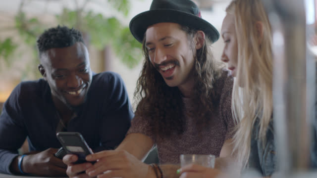 three hip young friends talk and laugh as they look at smartphone at happy hour in austin, texas bar. - three people stock videos & royalty-free footage