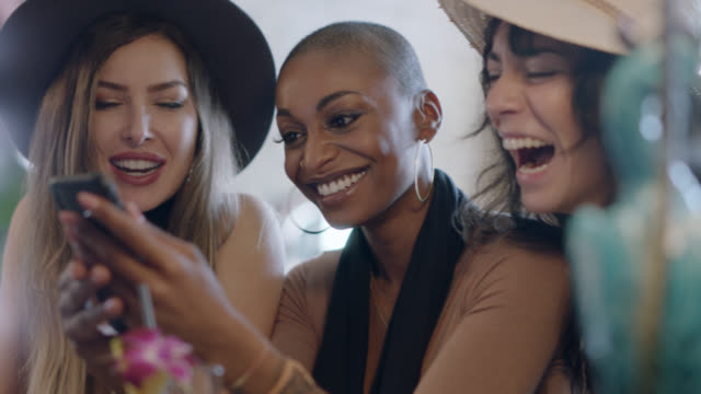 three hip young women chat and laugh as they look at smartphone at happy hour in local bar. - generazione y video stock e b–roll