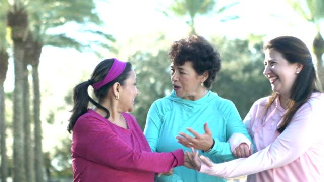 three hispanic women walking, talking in park - sweatshirt stock videos & royalty-free footage