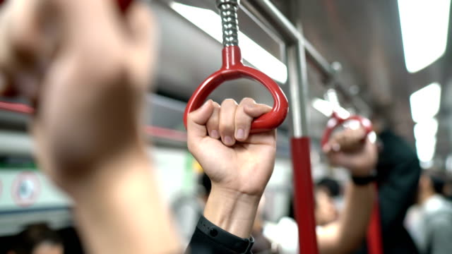 three human hands holding handrail or grip straps in subway or train - ora di punta video stock e b–roll