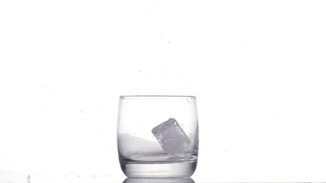 vídeos de stock e filmes b-roll de three ice cubes falling into glass against white background, slow motion - copo