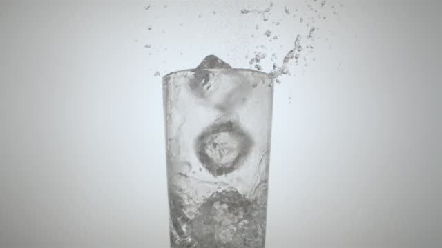 vídeos de stock, filmes e b-roll de ms slow motion three ice cubes falling into glass and splashing water/ glass falling over/ new york, new york - copo