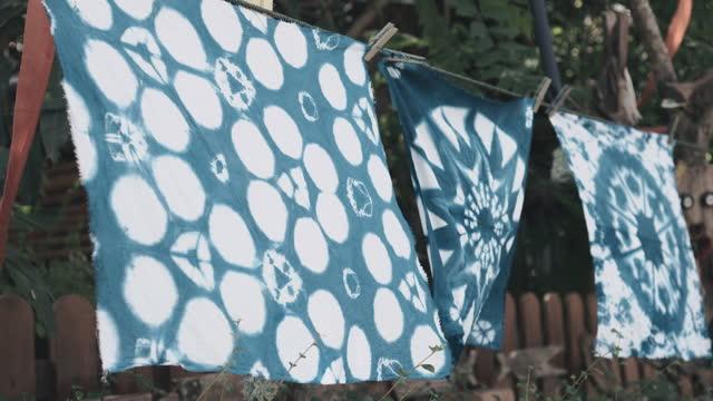 stockvideo's en b-roll-footage met drie indigo-geverfde hankerchieves die door sof wind worden geswayen - bloemenmotief