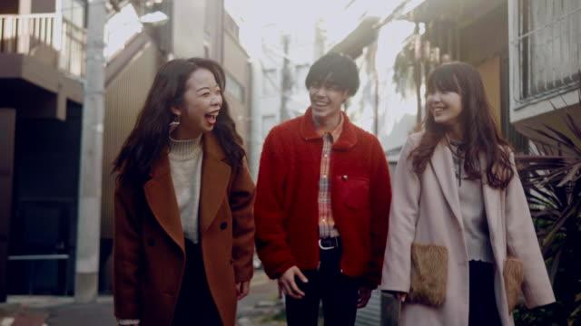 原宿で歩いて話す3人の日本人の友人 - ティーンエイジャー点の映像素材/bロール