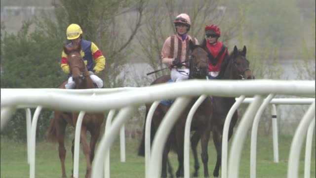 SLO MO WS Three jockeys on horses walking side by side at Newbury Racecourse / Newbury, England, UK