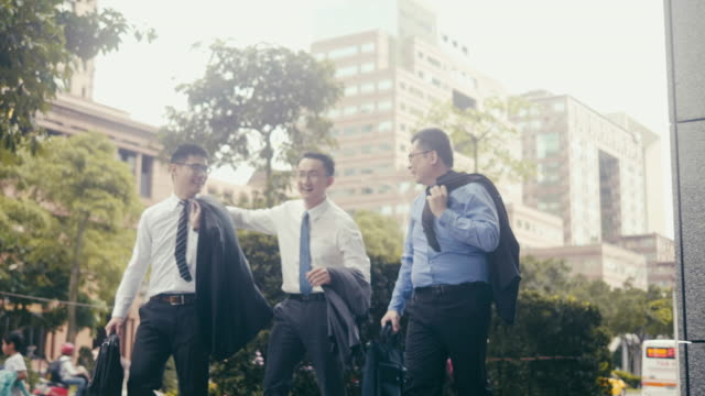 three joyful asian businessmen having a laugh while walking in the street - arm around stock videos & royalty-free footage