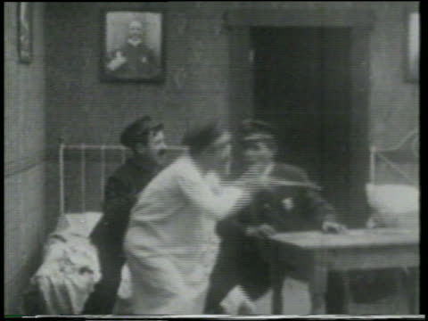stockvideo's en b-roll-footage met b/w 1915 three keystone kops in bedroom looking at thru telescope anxiously / short - 1915