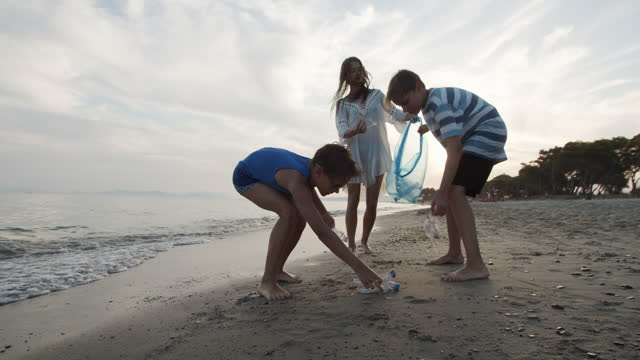 vídeos de stock e filmes b-roll de three kids cleaning up the beach - sustainable resources