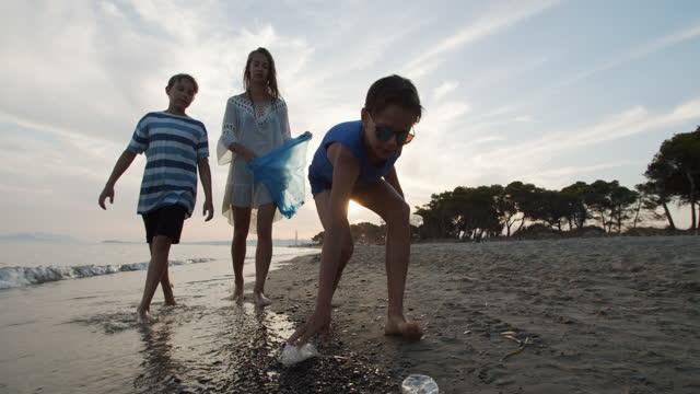 vídeos de stock, filmes e b-roll de três crianças limpando a praia - clean