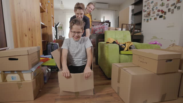vídeos de stock, filmes e b-roll de três crianças durante a mudança de casa estão andando em caixas de papelão - caixa de papelão